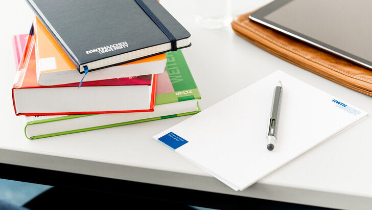 Books, paper and tablet on a desk